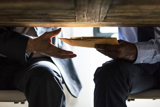 Empresarios enviando documentos debajo de la mesa.