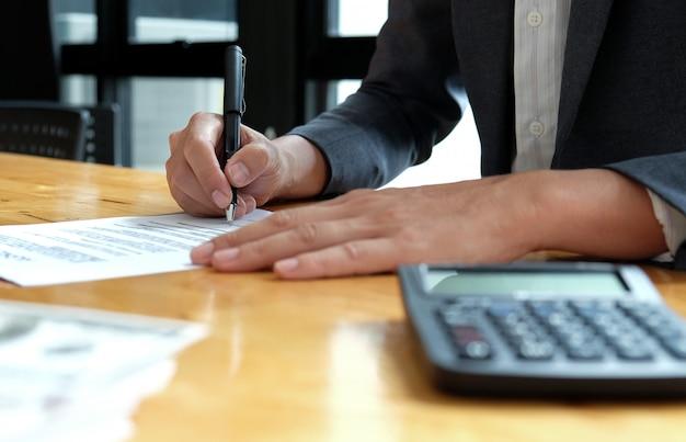 Los empresarios están firmando los documentos del contrato en la oficina.