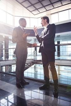 Los empresarios están hablando mientras está de pie en la oficina moderna.
