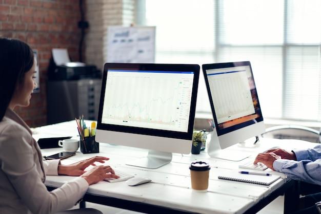 Los empresarios están observando las acciones de la compañía en la oficina.