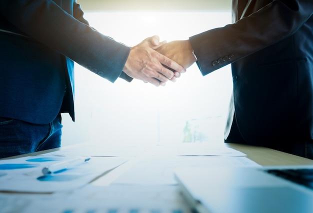 Empresarios estrechar la mano durante una reunión.