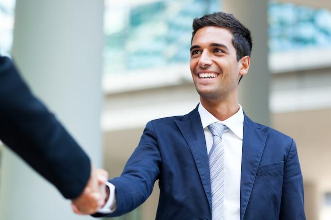 Empresarios estrecharme la mano al aire libre