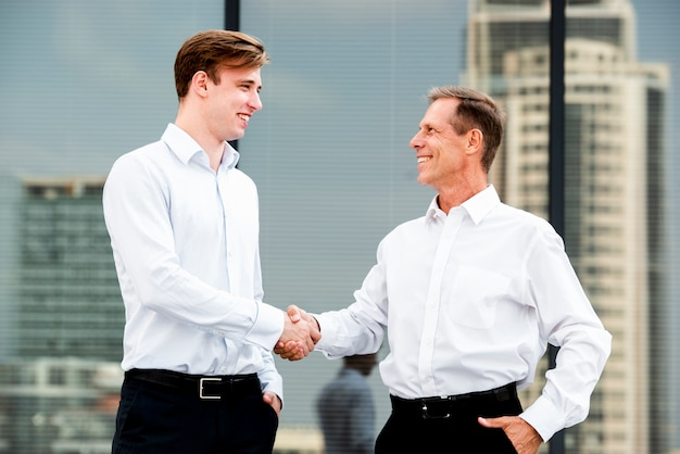 Empresarios estrecharme la mano cerca del edificio de cristal