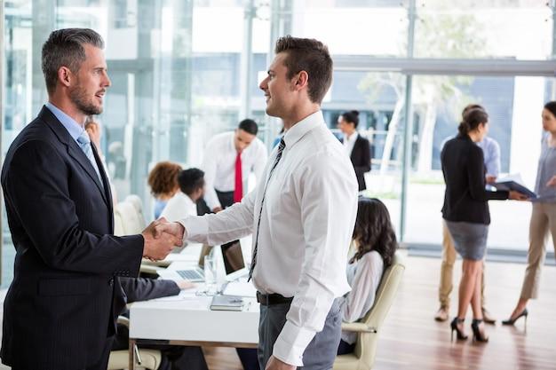Empresarios estrecharme la mano en la oficina
