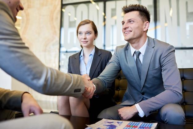 Empresarios estrecharme la mano en la reunión