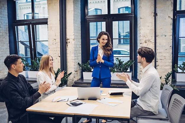 Empresarios exitosos aplaudiendo a la mesa en la oficina
