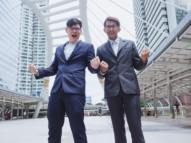 Empresarios exitosos con los brazos en alto celebrando su victoria en la ciudad