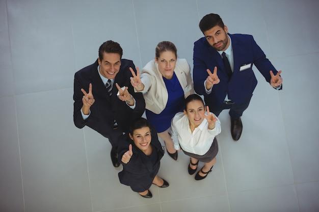 Empresarios exitosos que muestran el signo de la victoria