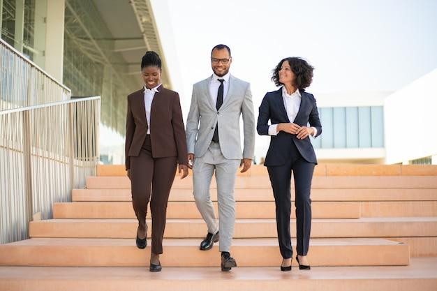 Empresarios felices caminando cerca del edificio de oficinas