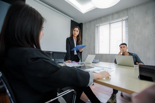 Empresarios y grupos asiáticos que usan un cuaderno para conocer en serio el trabajo