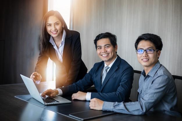 Empresarios y grupos asiáticos que usan un cuaderno para socios comerciales que discuten documentos e ideas en una reunión y mujeres de negocios que sonríen felices por trabajar