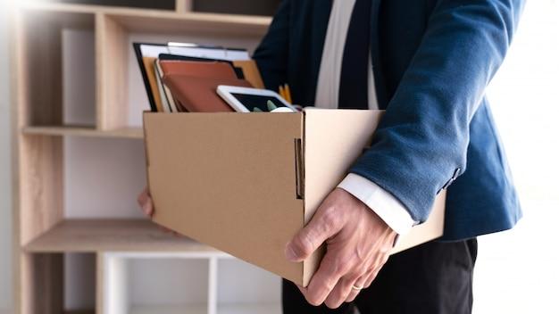 Empresarios guardando sus cosas en una caja de cartón