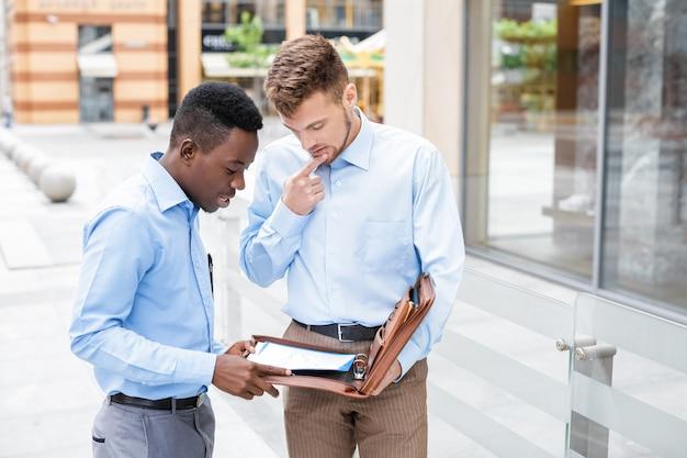 Empresarios hablando y mirando documentos