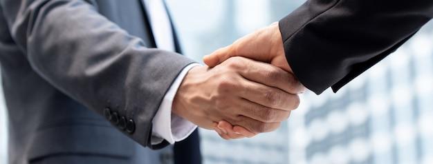 Empresarios haciendo apretón de manos en la ciudad.