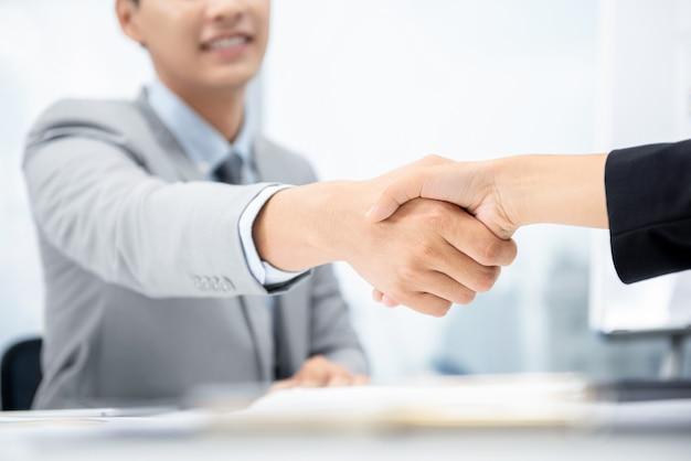 Empresarios haciendo apretón de manos en la sala de reuniones en la oficina de la ciudad