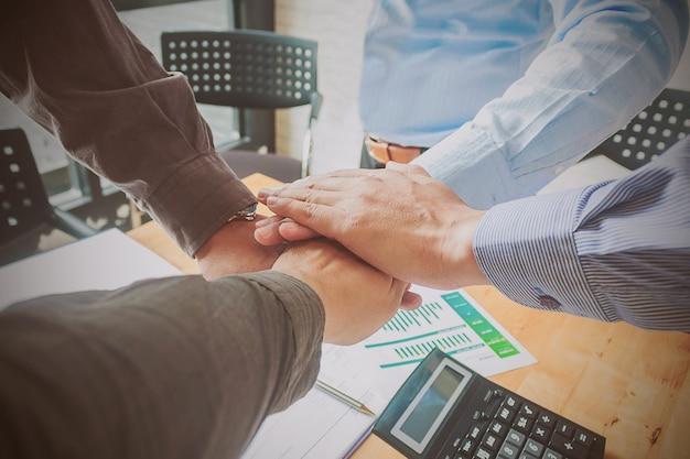 Empresarios haciendo pila de manos, enfoque suave