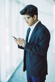 Empresarios indios asiáticos enviando mensajes de texto con un teléfono inteligente mientras camina en la oficina moderna