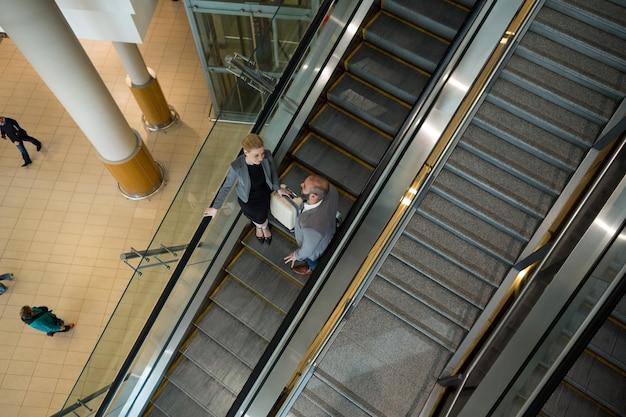 Los empresarios interactúan entre sí mientras bajan por la escalera mecánica