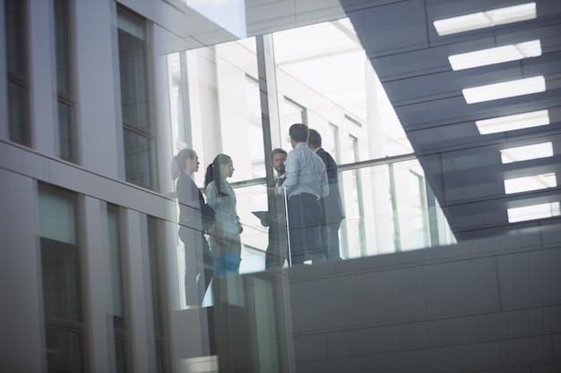Empresarios interactuando dentro del edificio de oficinas