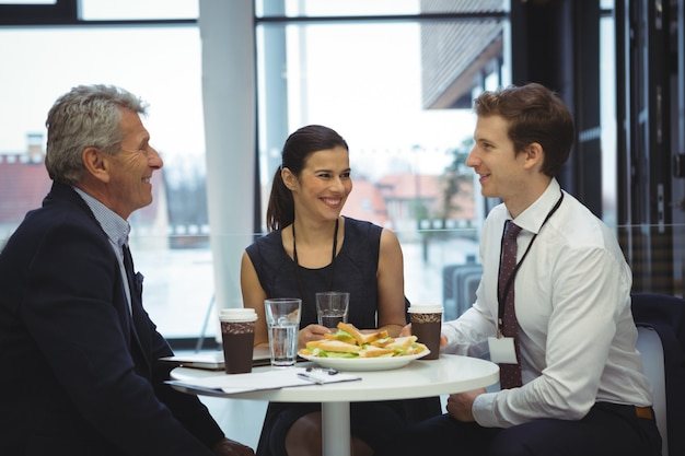 Empresarios interactuando mientras desayunan