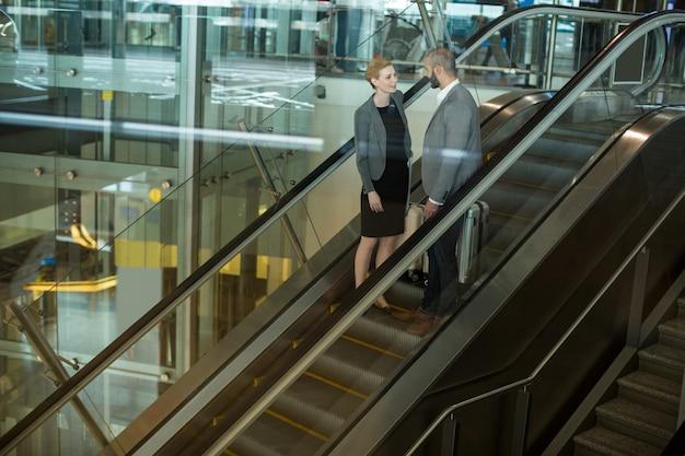 Empresarios interactuando entre sí mientras suben la escalera mecánica