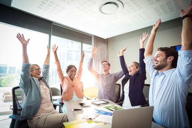 Empresarios levantando los brazos