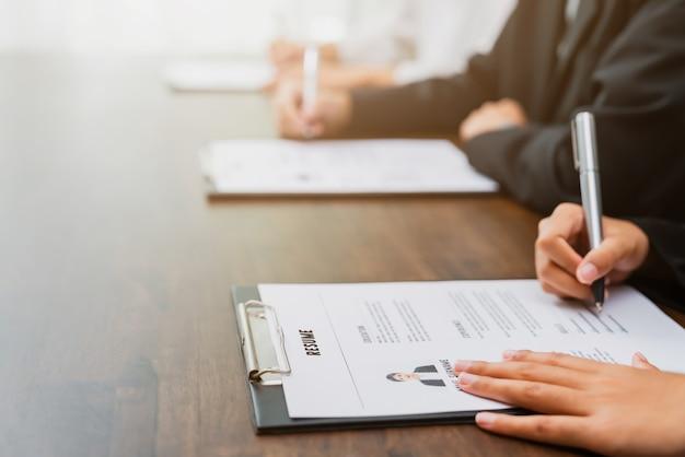 Los empresarios llenan la información de la solicitud de currículum vitae en el escritorio, presenta la capacidad de que la empresa esté de acuerdo con el puesto del trabajo.