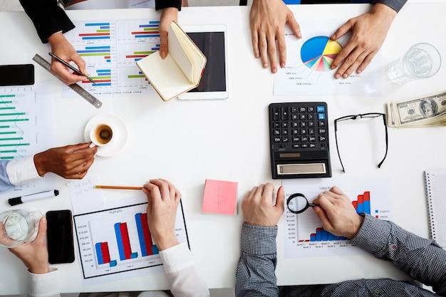 Empresarios manos en mesa blanca con documentos y borradores