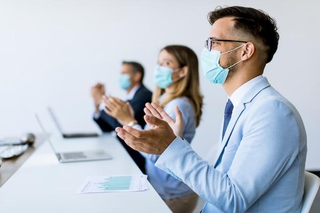 Empresarios con máscaras de protección aplaudiendo después de una exitosa reunión de negocios en la oficina moderna