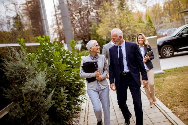 Empresarios mayores y jóvenes caminando al aire libre