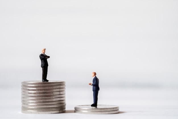 Los empresarios en miniatura se colocan en la pila de monedas de dinero. el efectivo es el concepto financiero rey y más comprar p