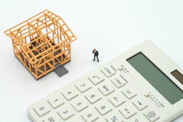 Empresarios en miniatura de pie análisis de inversión vivienda o inversión