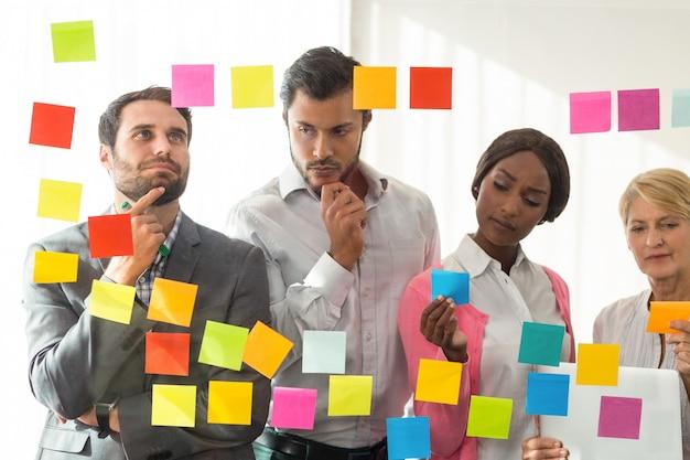Empresarios mirando notas adhesivas