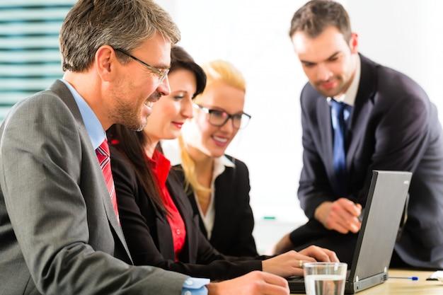 Empresarios mirando la pantalla del portátil