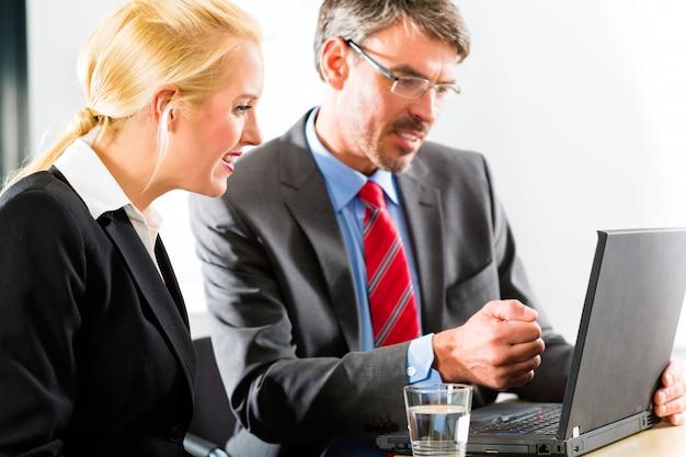 Empresarios mirando portátil en consulta