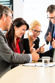 Empresarios mirando portátil con éxito
