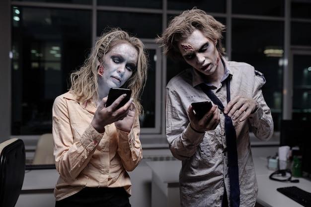 Empresarios muertos y espeluznantes con pintura de grasa zombie en sus caras y manos desplazándose en teléfonos inteligentes en la oficina en la medianoche