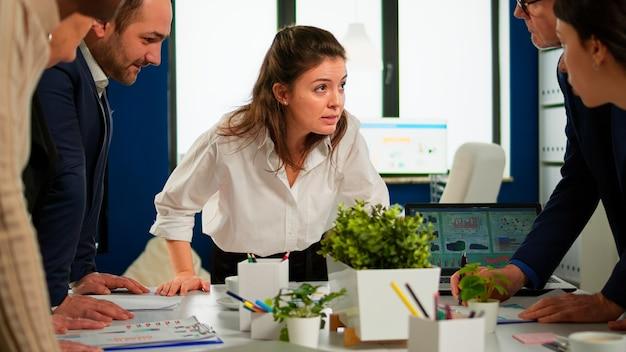 Empresarios multiétnicos analizando proyecto financiero durante la reunión corporativa. equipo de empleados en grupo que escucha a un colega que comparte ideas discutiendo el nuevo plan de marketing comparando datos en la sala amplia.