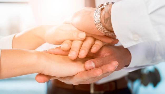 Empresarios multirraciales apilando las manos unos sobre otros