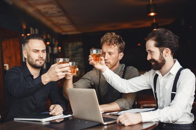 Empresarios en negociaciones. hombres con alcohol sentados a la mesa. los amigos están hablando.
