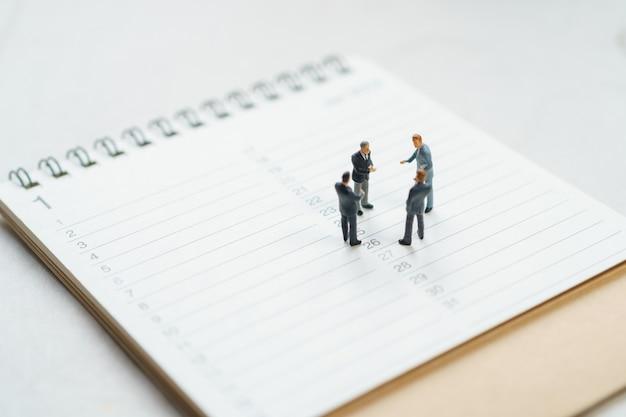 Empresarios de personas en miniatura en calendario blanco