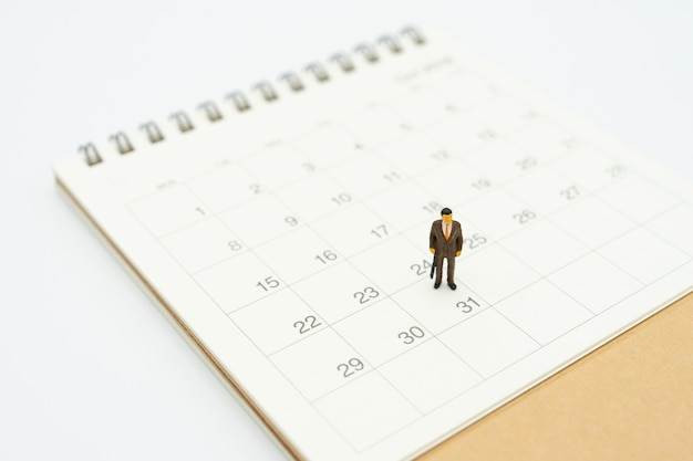Empresarios de personas en miniatura de pie en el calendario blanco