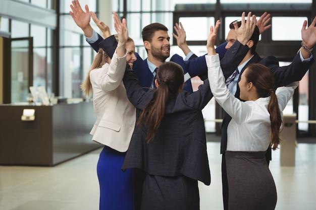 Empresarios de pie junto con los brazos arriba
