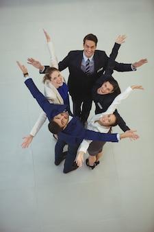 Los empresarios de pie junto con los brazos extendidos