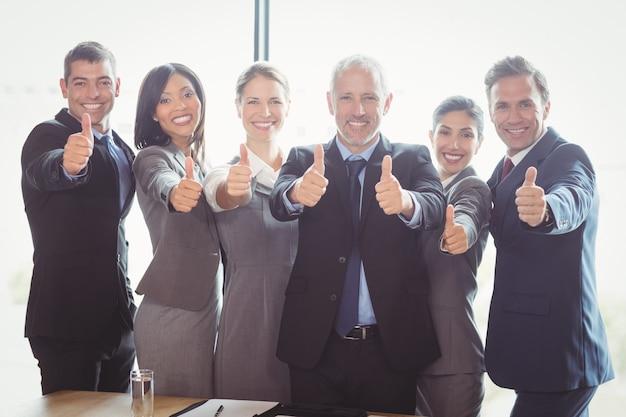Empresarios de pie juntos y dando pulgares arriba