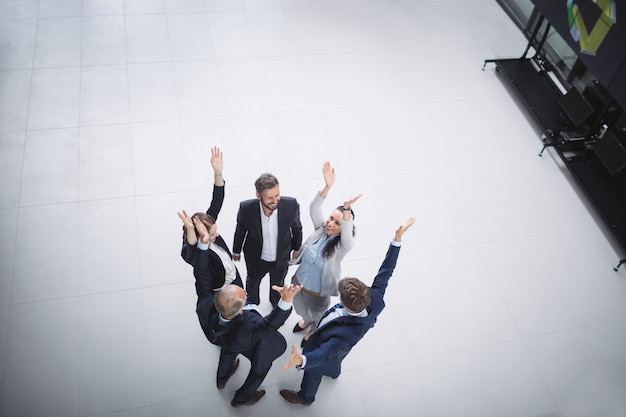 Empresarios de pie con las manos levantadas