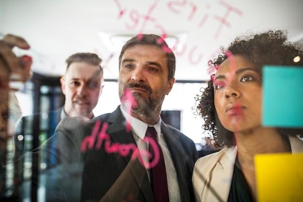 Empresarios planeando en una pared de vidrio