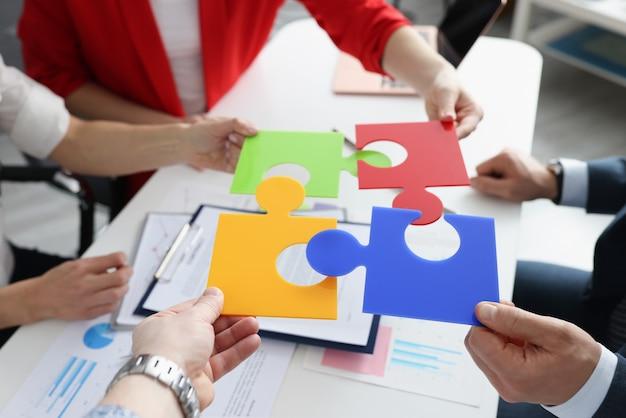 Los empresarios ponen rompecabezas multicolores en uno. nuevas ideas para el concepto de desarrollo empresarial