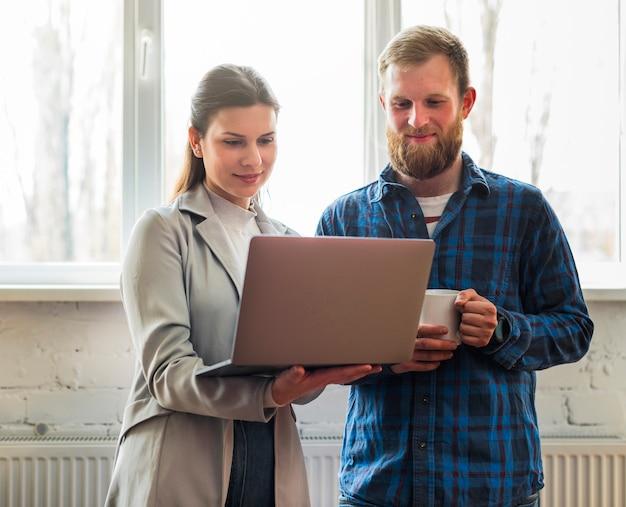 Empresarios profesionales felices que miran el ordenador portátil en oficina