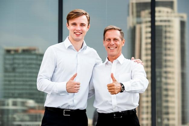 Empresarios pulgares arriba gesto cerca del edificio